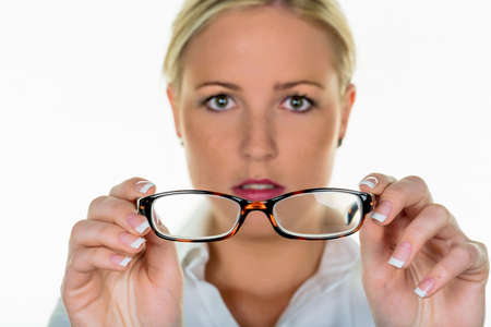 visually: a woman holding glasses in hand. symbolic photo for poor vision and refractive error