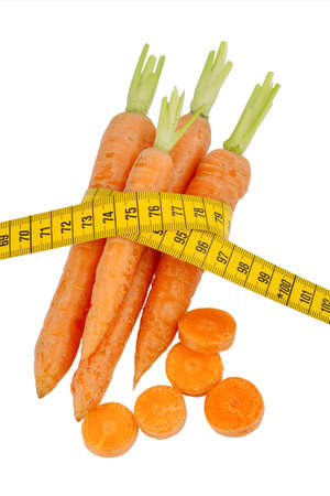 organically: organically grown carrots with tape measure. fresh vegetables and fruits is always healthy. symbolic photo for healthy diet. Stock Photo