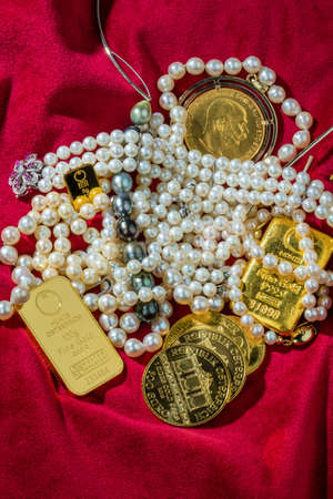 monetary devaluation: gold in coins and bars with decorations on red velvet. symbolic photo for wealth, luxury, wealth tax.