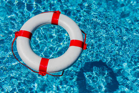 budget crisis: an emergency tire floating in a pool. symbolic photo for rescue and crisis management in the financial crisis and banking crisis.