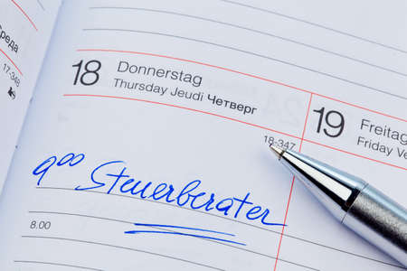 auditors: an appointment is entered on a calendar: tax consultants Stock Photo