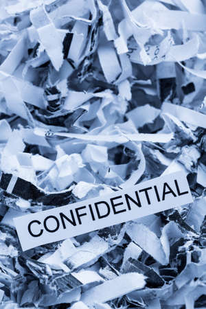 paper shredder: papierschnitzel tagged confidential, symbol photo for data destruction, banking secrecy and confidentiality