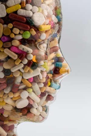 ein Kopf aus Glas mit vielen Tabletten gefüllt. Foto Symbol für Drogenmissbrauch und Schmerzmittel.