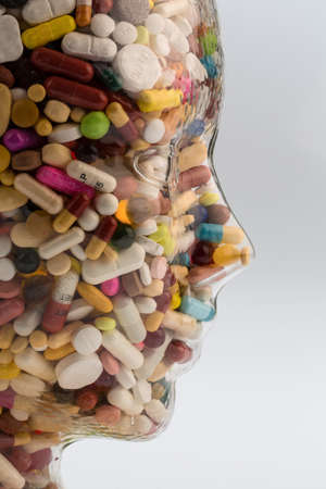 a head made of glass filled with many tablets. photo icon for drugs abuse and painkillers.