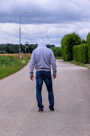 unrelated: a man walks on a lonely road. Stock Photo