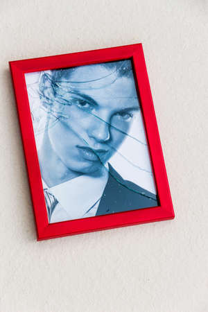 unfaithful: zerbrochner picture frame. symbolic photo for divorce, separation and relationship crisis Stock Photo