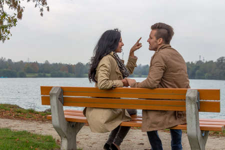 vivre: a young, verl liebtes couple sitting on a park bench