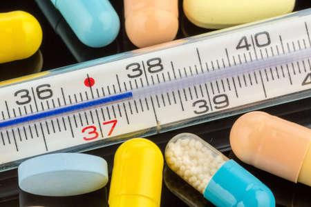 thermometer: un termómetro y tabletas. foto simbólica de gripe y los resfriados Foto de archivo