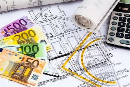 drawing a plan: a blueprint of an architect with a calculator and euro money. symbolic photo for funding and planning of a new home.