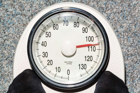 kg: on a personal scale is a fat person. symbolic photo for overweight and fettlleibigkeit.