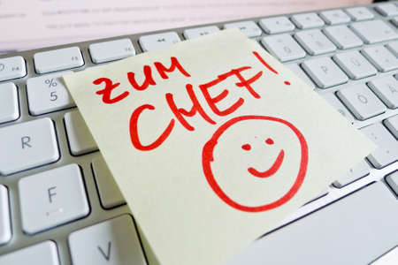 revaluation: a memo is on the keyboard of a computer as a reminder: for chef Stock Photo