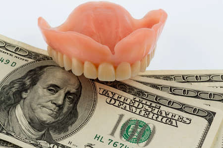 dentures: dentures and dollar bills symbol photo for dentures, treatment costs and payment
