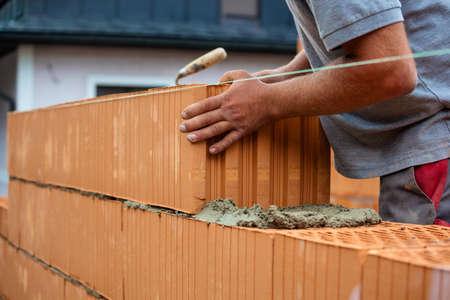anonieme bouwvakker op een bouwplaats tijdens de bouw richtte een muur van bakstenen. bakstenen muur van een massief gebouw. symbool foto voor illegale arbeid en botch