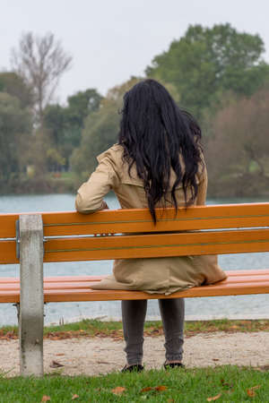 withdrawn: a young woman sitting pensively on a park bench Stock Photo