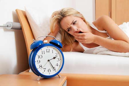 Schlaflosigkeit mit Uhr in der Nacht. Frau kann nicht schlafen. Standard-Bild