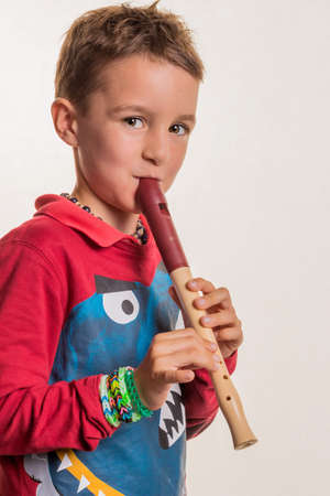 music education: a child playing on a flute on wood. music education and music school. Stock Photo