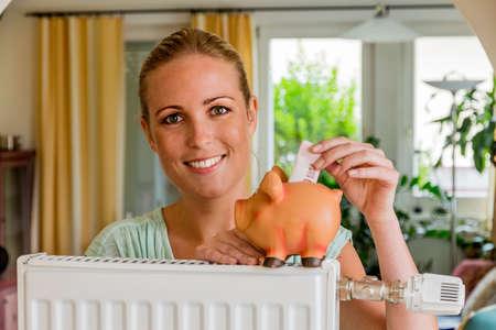 radiador: una mujer joven con un radiador y una alcancía. Foto simbólica para el ahorro de energía y calefacción