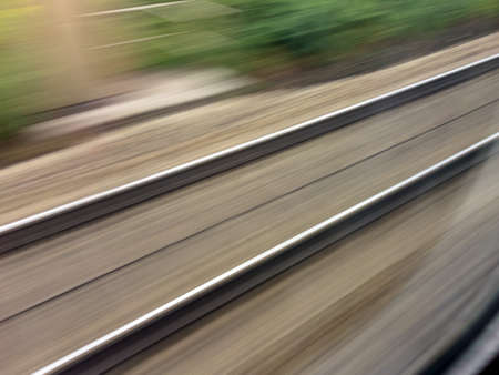 tempo: tracks and rails out in movement from a moving train. symbolic photo for train, tempo and dynamics.