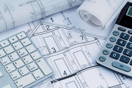 un progetto di un architetto con una calcolatrice. Foto simbolica per il finanziamento e la pianificazione di una nuova casa.