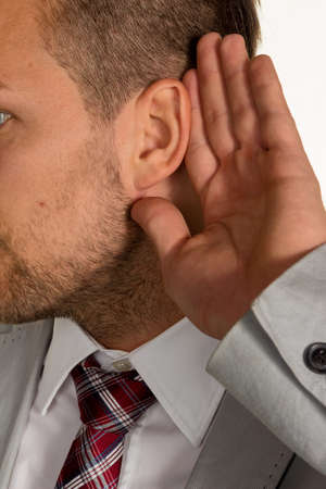 insider information: a man (business owner or manager) holds his hand to his ear