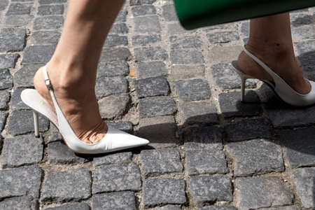 feet of a woman with high heels on a pavement