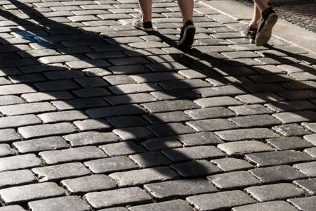 shadows of people on a pavement