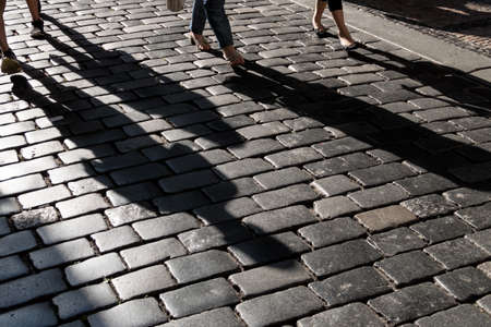 peoplesoft: shadows of people on a pavement
