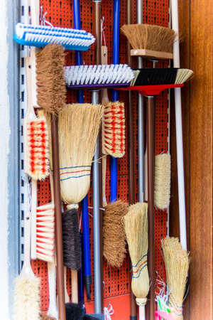 cleaning crew: cabinet with different types of brooms