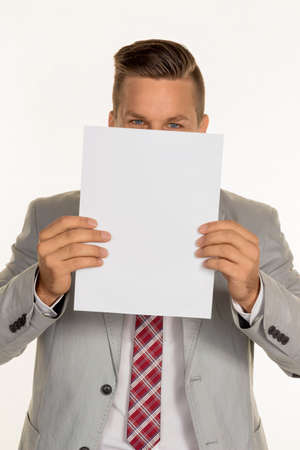 vacate: a young businessman holding a blank sheet over her face. Stock Photo