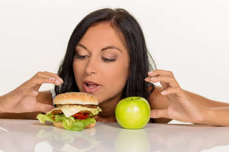 reduction: a young woman can not decide between a hamburger and an apple itself. healthy or unhealthy diet.