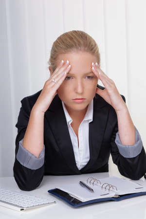 work stress: a young woman with migraine and headache sitting in an office.