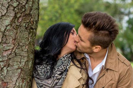 parejas enamoradas: un joven, Verl liebtes mujer mirando desde detrás de un árbol