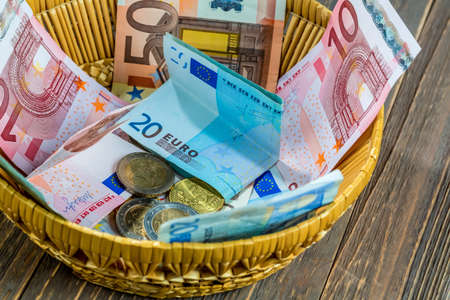 contributions: a basket with money for donations and gratuities Stock Photo
