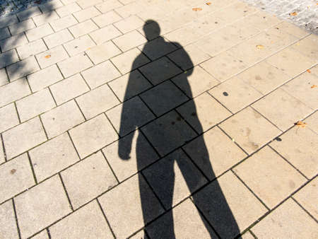 anonym: the shadow of a man on a sidewalk. anonymity of the big city. Stock Photo