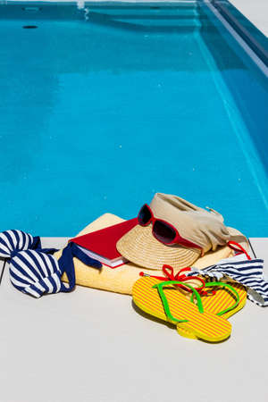 beach holiday: utensils for a nice relaxing vacation day lying next to a swimming pool. relaxation on vacation. Stock Photo