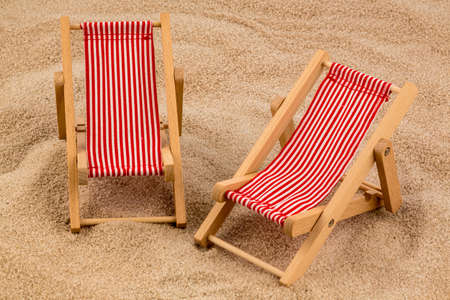 holiday profits: a small deck chair (model) on a sandy beach. symbolic photo for vacation, holiday, travel