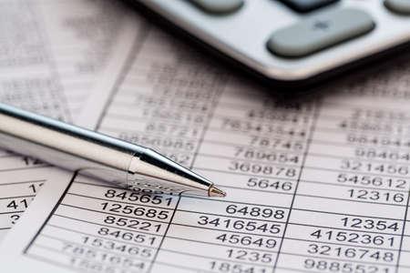 une calculatrice est situé sur les numéros un équilibre statistiques américaines. photo icône de ventes, des bénéfices et des coûts. Banque d'images