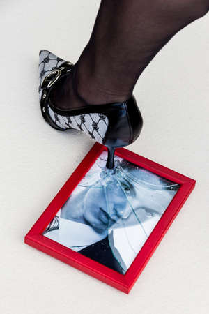 unfaithful: broken picture frames and high heels. symbolic photo for divorce, separation and relationship crisis Stock Photo