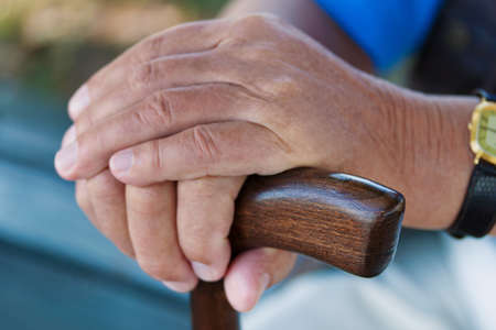 walking stick: hand of an elderly man with a walking stick. senior with disabilities Stock Photo