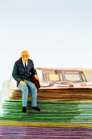 symbolic photo for retirement and old-age security, figure an old man sitting on a stack of bills Stock Photo