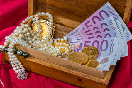 namacalny: gold in coins and bars with decorations on red velvet. symbolic photo for wealth, luxury, wealth tax.