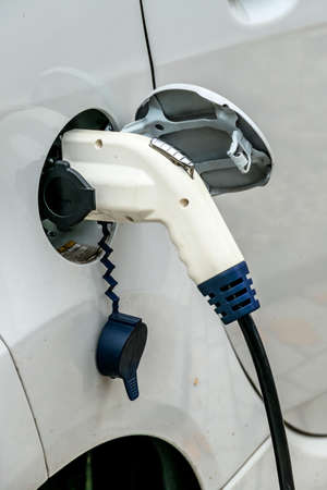 pkw: electric car at charging station. symbol of ecology, climate change, innovation