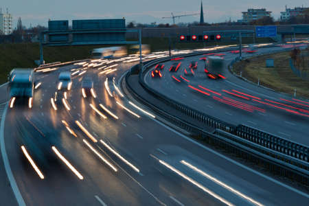 fcc: many cars are driving at night on a highway and create light trails.