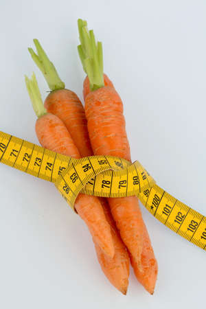 thinness: organically grown carrots with tape measure. fresh vegetables and fruits is always healthy. symbolic photo for healthy diet. Stock Photo