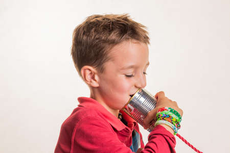 notieren: child listens in a tin can phone.