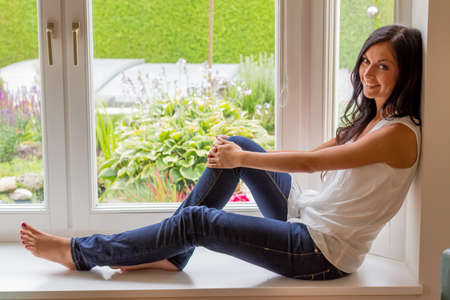 relaxen: a young woman sitting at the window and relax Stock Photo