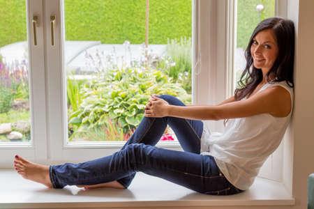 mujer sentada: una joven mujer sentada junto a la ventana y relajarse
