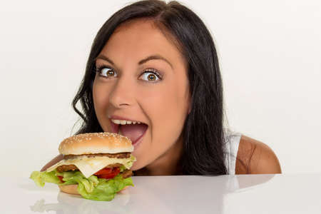 fast: a young woman with a hamburger. fast food and fast food