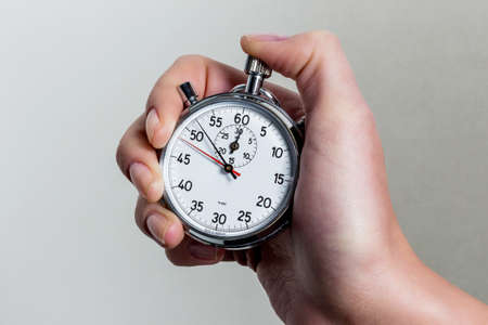 clockwise: a hand holding a stopwatch.