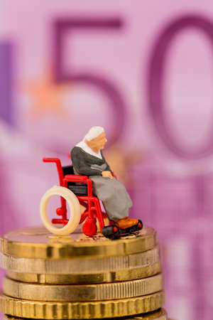 nursing allowance: woman in wheelchair on money stack, symbol photo for disability, attendance allowance and expenses public health Stock Photo
